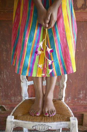 花を持って椅子にドレス立って女性の低いセクション