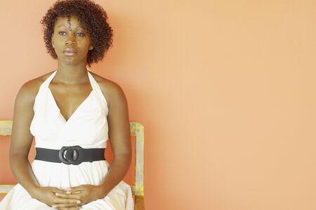Portrait of woman in white dress sitting