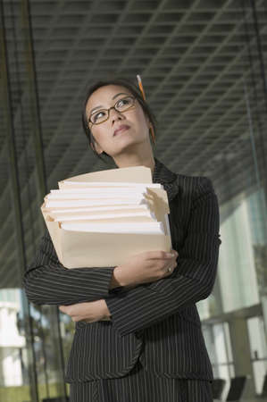 Businesswoman holding stack of paperwork Stock Photo - 16072999
