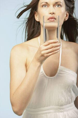 above 21: Portrait of woman holding glass of water to mouth LANG_EVOIMAGES