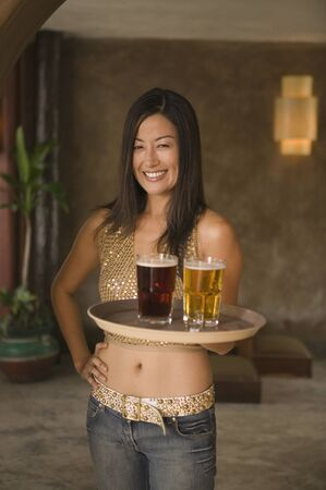 Portrait of woman holding tray of drinks