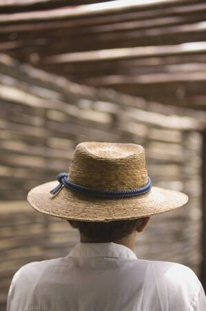 above 30: Rear view portrait of man wearing straw hat LANG_EVOIMAGES