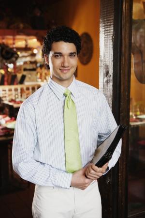 Portrait of waiter holding menus in restaurant 스톡 콘텐츠