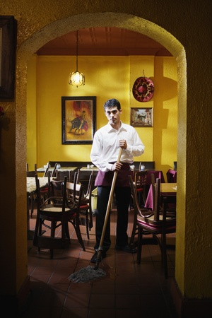 above 30: Portrait of man mopping restaurant floor LANG_EVOIMAGES
