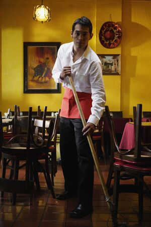 above 25: Portrait of man mopping restaurant floor LANG_EVOIMAGES