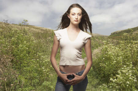 Portrait of woman standing with thumbs hooked in jeans Stock Photo - 16073107