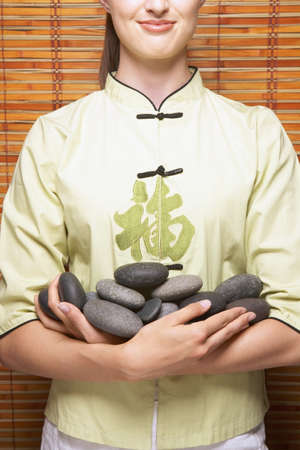 Mid section portrait of woman holding pile of rocks Stock Photo - 16073111