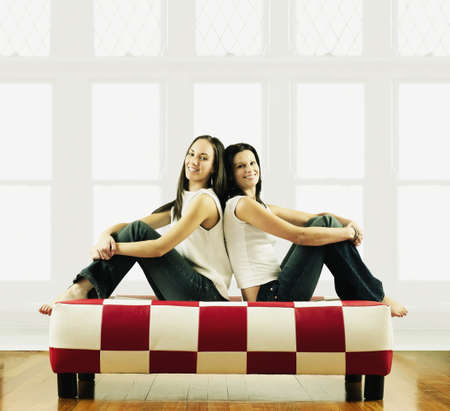 kinfolk: Two young women sitting back to back