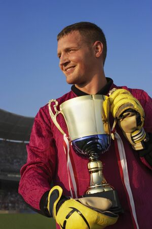 Male goalie triumphantly holding trophy 版權商用圖片