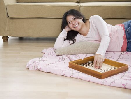 bedcover: Young woman playing backgammon on living room floor LANG_EVOIMAGES