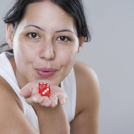 Young woman blowing on dice for luck Stock Photo - 16073155