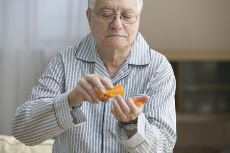 ninetys: Older man shaking out pills into his hand