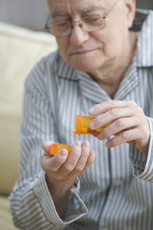 Older man shaking out pills into his hand Stock Photo - 16073158