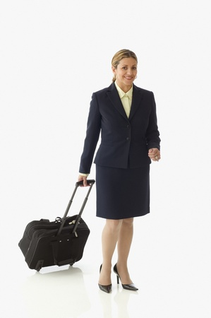 being the case: Middle aged businesswoman posing for the camera with rolling suitcase