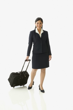 tugging: Businesswoman posing for the camera with rolling luggage LANG_EVOIMAGES