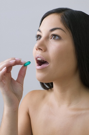 Young woman taking a pill Stock Photo - 16073163