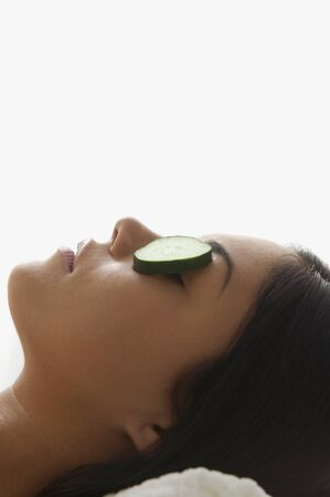 Young woman resting with cucumbers on her eyes Stock Photo - 16073170
