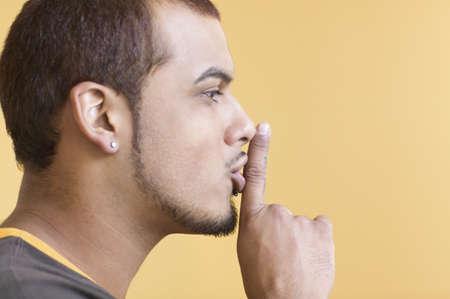 motioning: Young man making Îshh sound