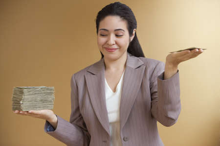 front raise: Businesswoman holding uneven stacks of money in both hands