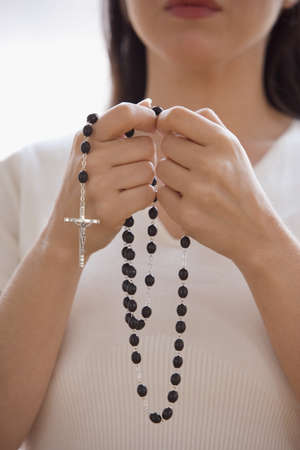 lower section view: Woman praying with rosary beads