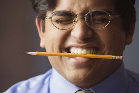 Businessman holding a pencil between his teeth Stock Photo - 16073285