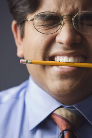 Businessman holding a pencil between his teeth Stock Photo - 16073286