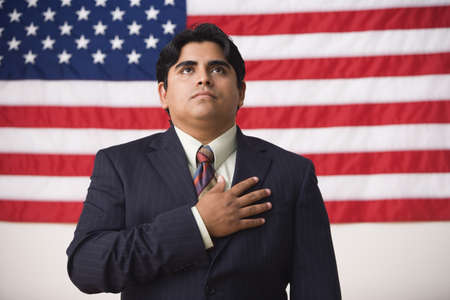 citizenship: Businessman standing in front of an American flag with one hand across his heart