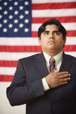 thirty's: Businessman standing in front of an American flag with one hand across his heart