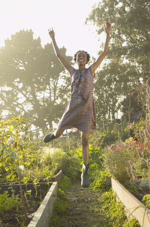 Young woman jumping for joy in a garden Stock Photo - 16073308