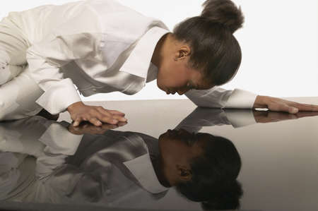 Young woman looking at her own reflection in the floor Stock Photo - 16073320