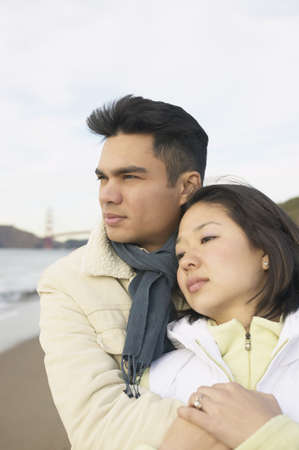idealistic: Young couple hugging on the beach