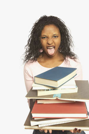 whining: Teenage girl sticking her tongue out behind a pile of books LANG_EVOIMAGES