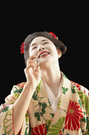 Asian woman in ethnic clothes talking on her cell phone Stock Photo - 16073358