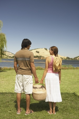 stepping: Couple holding a picnic basket in a field LANG_EVOIMAGES