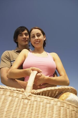 Low angle view of a couple holding a picnic basket Imagens