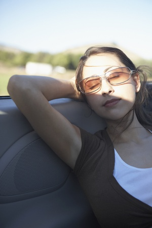 Young woman sleeping in a convertible
