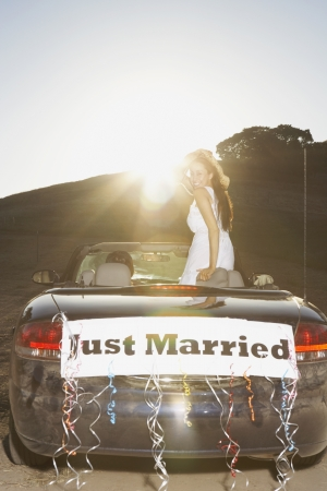 Bride standing in convertible with ÏJust MarriedÓ banner on the back
