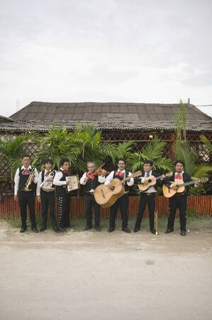 Mariachi band in front of building playing their instruments