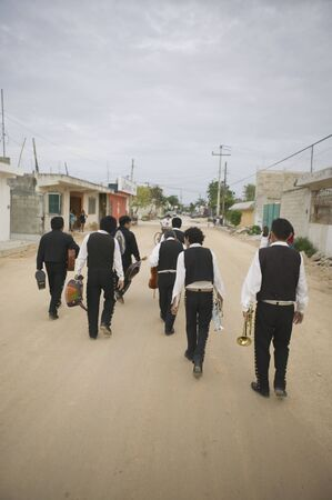 Mariachi band walking and carrying their instruments