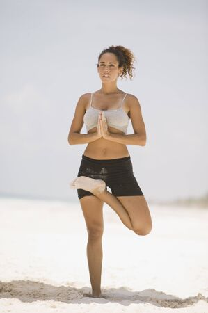 seriousness skill: Young woman practising yoga on the beach
