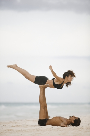 buddies: Couple practising gymnastics on the beach