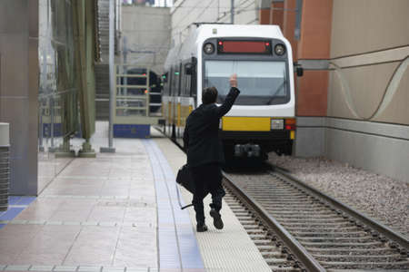 tardy: Businessman waving down a train
