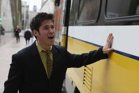 whining: Businessman hitting the side of a train to stop it