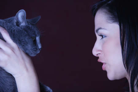Young woman talking to her cat Stock Photo - 16073499