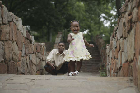 stepping: Father watching his baby daughter walk
