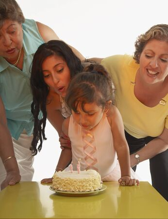 ninetys: Young girl blowing out candles on her birthday cake LANG_EVOIMAGES