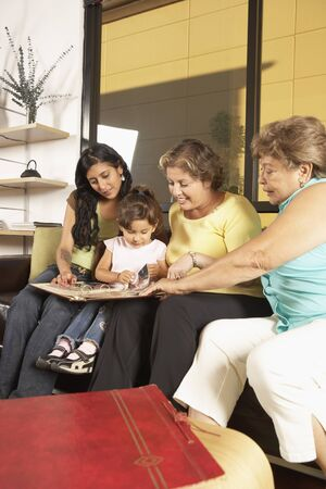 Female members of a family looking at a photo album together Stock Photo - 16073559