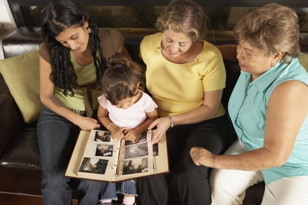 gramma: Female members of a family looking at a photo album together