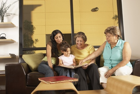 el salvadoran: Female members of a family looking at a photo album together
