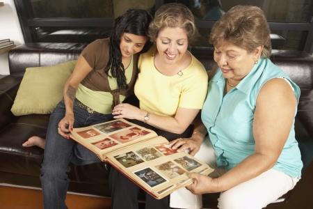 Vrouwelijke leden van een gezin op zoek naar een foto album samen Stockfoto